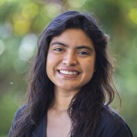 A portrait of Carolina Cruz smiling at the camera with blurred green plants in the background.
