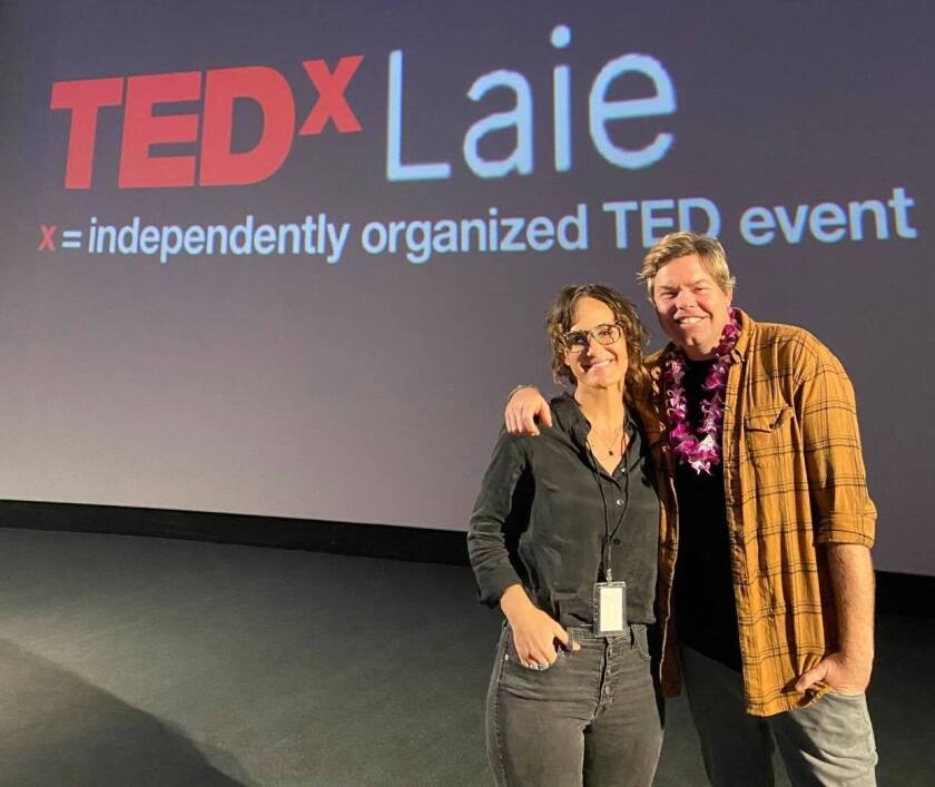 Richie and Natalie Norton stand on stage with the TEDxLaie logo in the background.