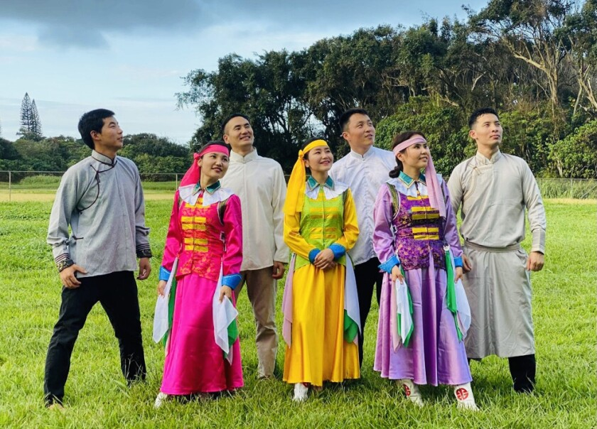 Gantulga stands in a green field wearing a yellow Mongolian dress with two other woman on either side of her wearing pink and purple Mongolian dresses and four men behind her wearing white/grey/off-white Mongolian shirts and pants.