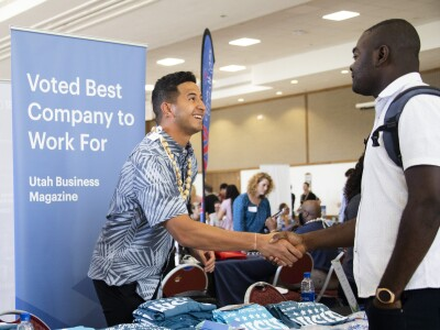 Two men shaking hands over a booth for the Domestic Career Fair.