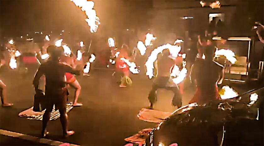 Samoan fire knife dancers line the street in front of Pulefano Galea'i's home on Kulanui Street in Laie.