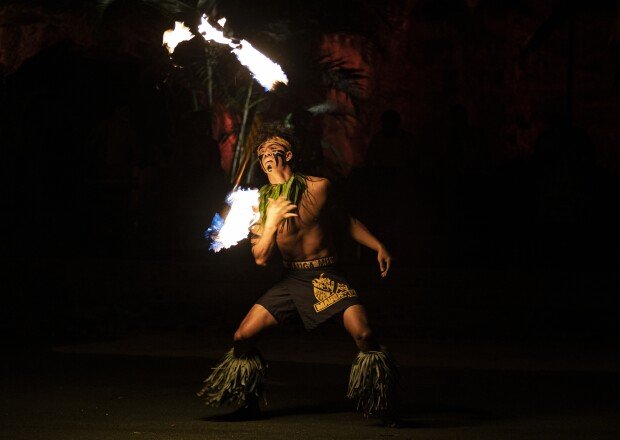 fireknife dancer twirls a fireknife in the air while wearing a black lavalava with yellow words and green leaves around his legs and neck.