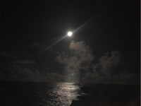 The bright moon in a dark sky over a moon lit ocean