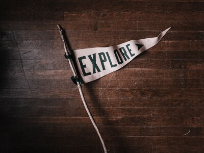 """Little triangular flag that says """"Explore"""" on it resting on a wooden background."""
