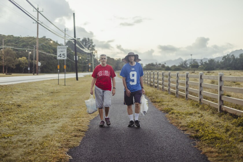 John and Rhonda Bell walking with trash bags on the bike path in Laie.