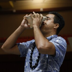 A young man wearing an aloha shirt and kukui nut lei while blowing a conch shell.
