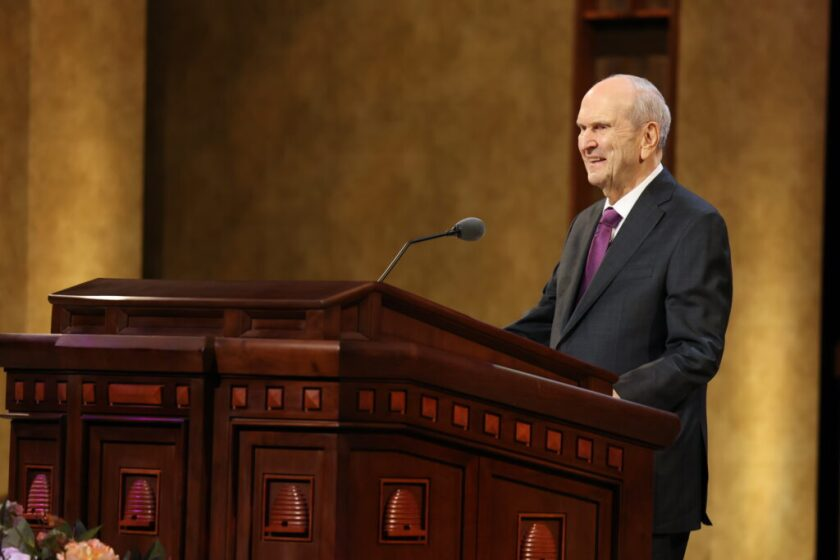 President Russell M. Nelson smiling speaking at a wooden pulpit with brown and tan lit-up walls behind him.