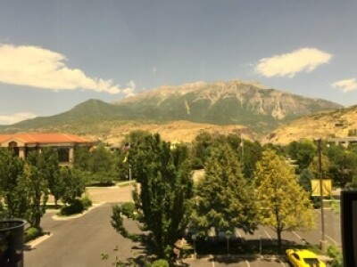 Photo of parking lot, trees, and mountains.