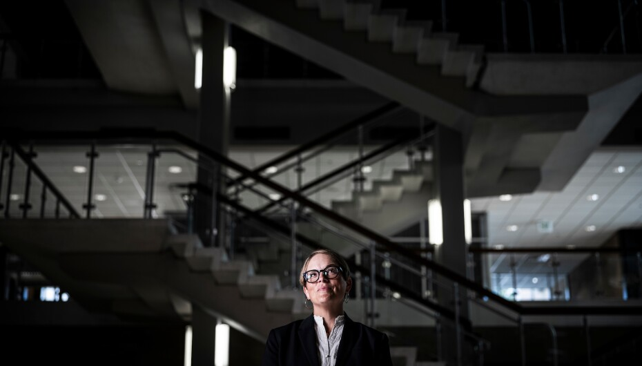 A professional portrait of Amy Jensen in front of the dimly-lit HFAC main floor stairs.