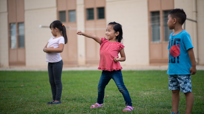 Three young Hopkido students stand on the grass in front the apartments they live in, and the middle girl, wearing a pink top and blue jeans, strikes a martial arts pose.