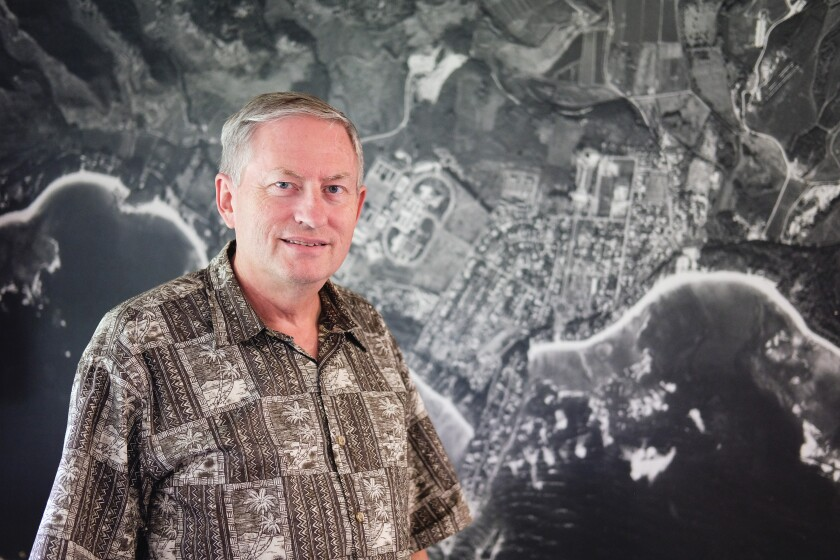 Brooks Haderlie stands in front of an older aerial photo of Laie
