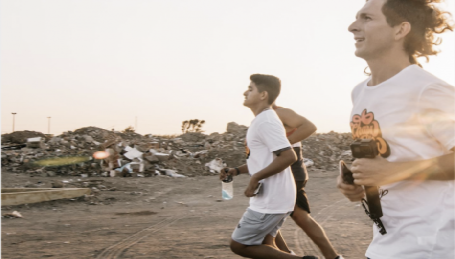 BYUH Alumnus Clayton Kearl runs with Peruvians next to piles of rubbish