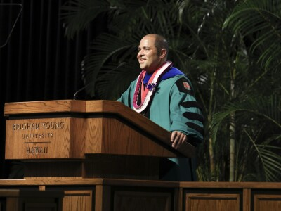 President John S.K. Kauwe III at the podium with academic robes