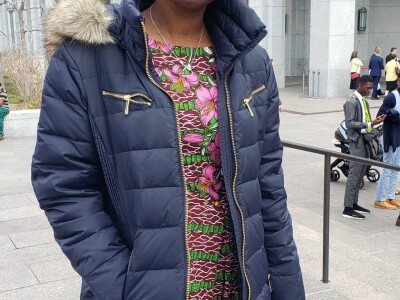 Rebecca Udoh in a dress and jacket standing in front of white building in Salt Lake City.