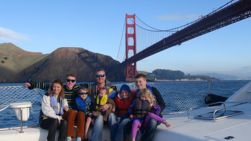 The Schafer Family  underneath the Golden Gate Bridge on their sailboat.