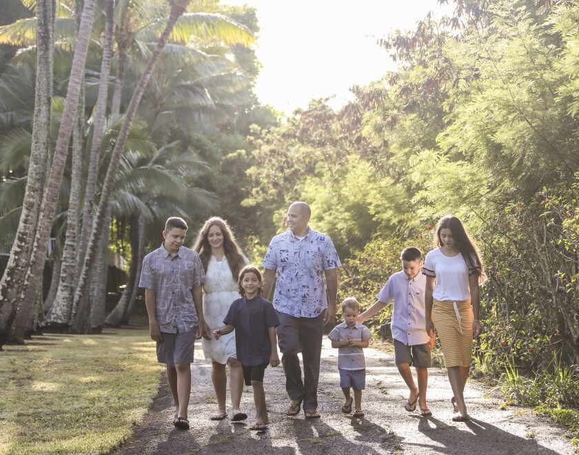 John and Monica Kauwe walk with their five children with the light shining through the palm trees in the background.