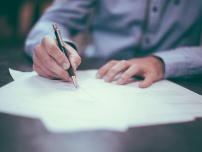 Image of man writing with a pen on paper on a table