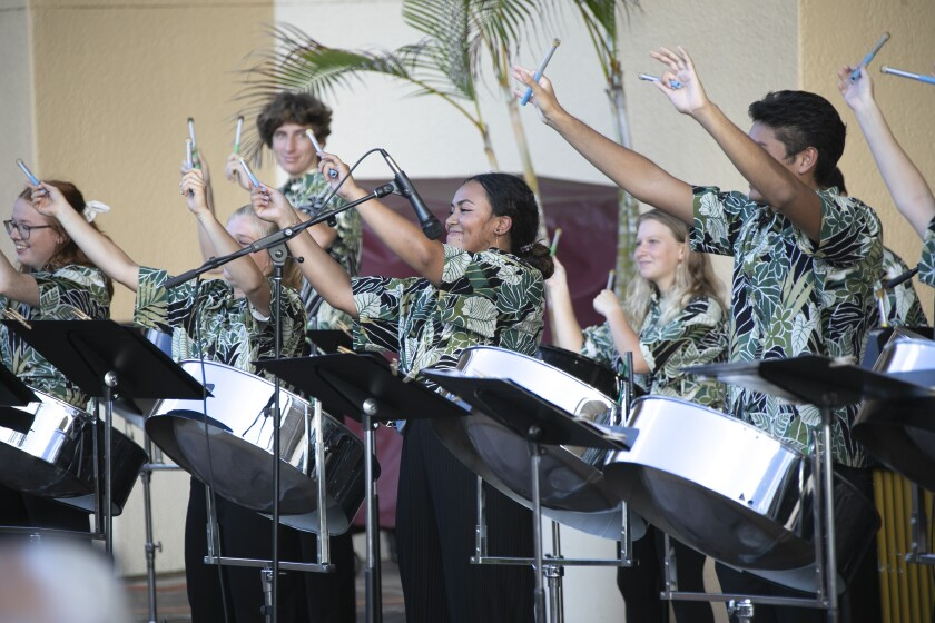 Band members wearing green-leaved shirts hold up their drum sticks and smile with metal steel drums in front of them.
