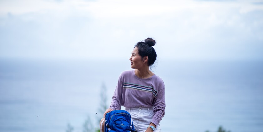 Dalaichuluun wearing a long-sleeved purple shir and white shorts holds her blue backpack in front of her looking out to the left with the ocean behind her.