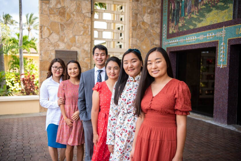 Five women and one man stand in a line wearing dresses and a suit smiling with the BYUH mural behind them and a tan stone wall.