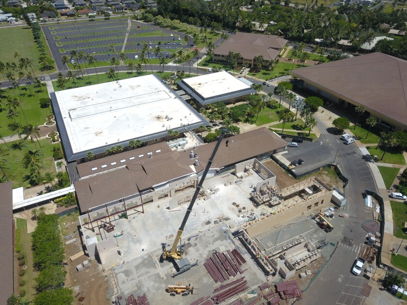A heavy crane is in the middle of the cafeteria construction. Piles of beams are under the crane. McKay Building is on the left-hand sie and the Academic Oval is on the right-hand side of the photo.