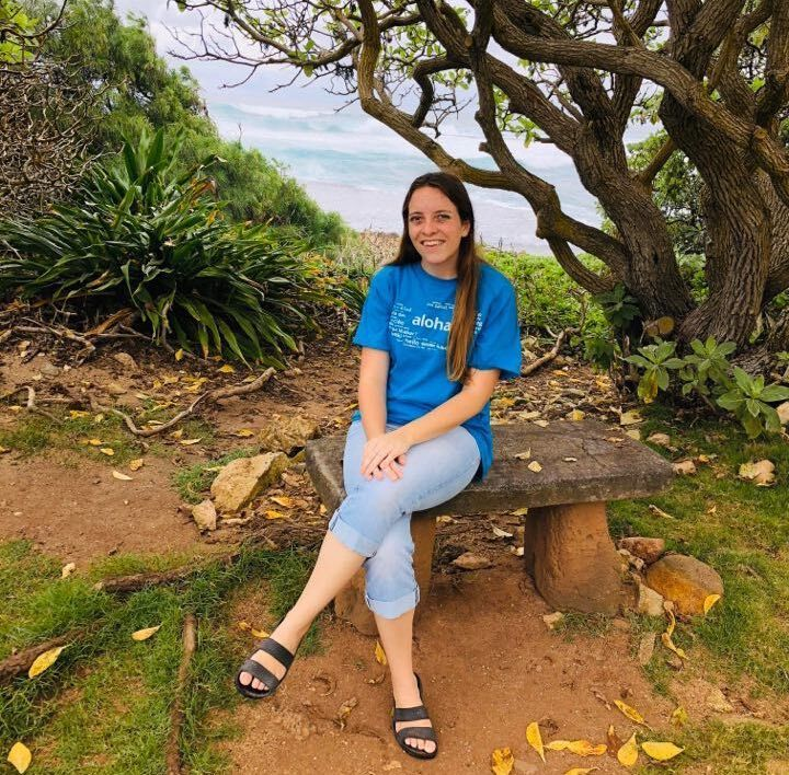 Diana Hawkins, wearing a blue shirt and pants, sits on a bench near the ocean.