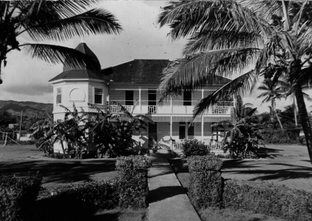 Black and white photo of a two-story Victorian-styled building with hedges and palm trees around it.