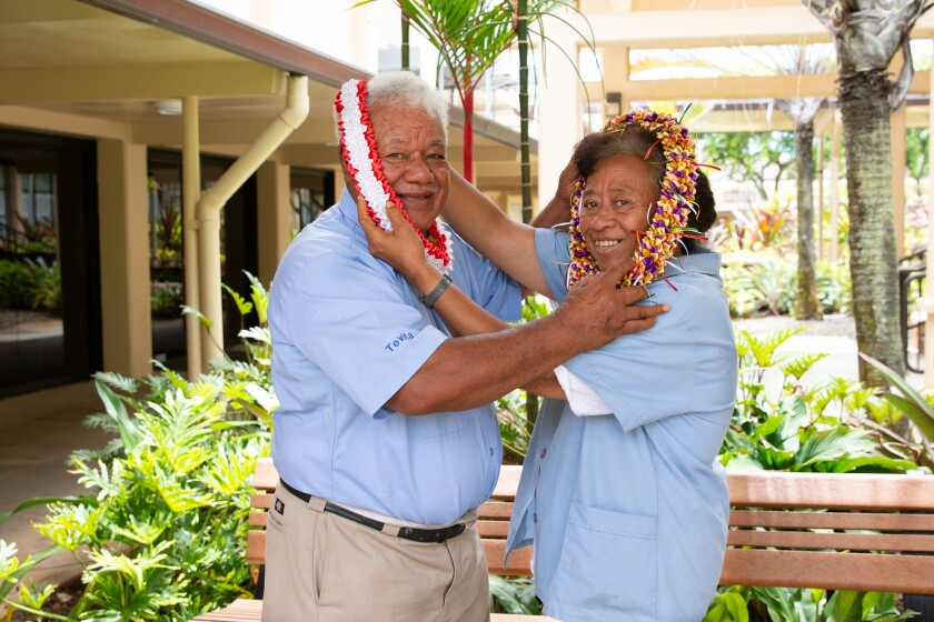 Tevita and Mele Lavulavu put colorful leis around each others' necks while wearing light blue button-up shirts with a hallway, bench and greenery behind them.