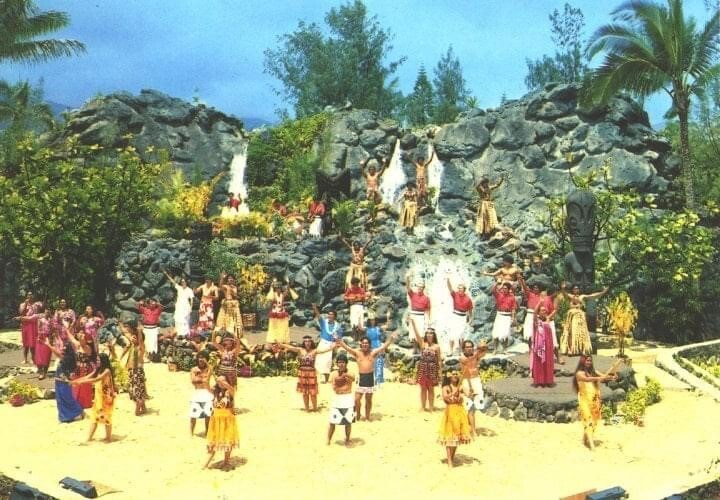Old photo of dancers wearing bright yellow, red and white outfits on a yellow ground with waterfalls behind them at the Polynesian Cultural Center.