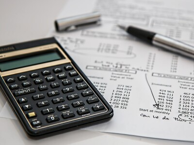 Image of a calculator on a table alongside a paper and pen