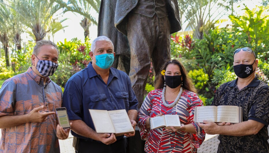 Ikua, Haverly, Housman, and Walk holding digital and print copies of scriptures and a book of hymns in the Hawaiian language.
