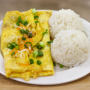 This is a photo of an omelette. Scallions, green onions, shredded cheese has been sprinkled on top. Two scoops of rice are on the side.