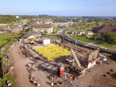 Overall aerial view of Science Building. Mikionele Way is on the left-hand side and Academic Oval is on the right-hand side of the photo. Stego moisture barriers are placed in preparation for slab on grade concrete pour. Two cranes are working on the walls.