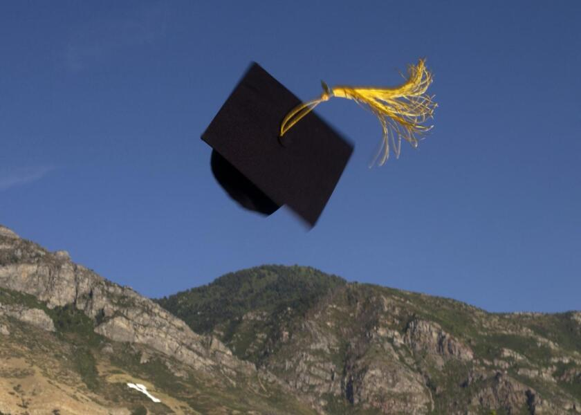 A Graduation cap thrown into the air in front of Y Mountain