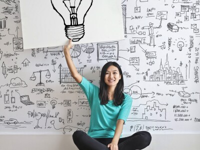 Woman holding a drawing of a light bulb