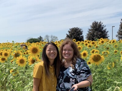 Marisa Firth stands in a sunflower field with her mother who is holding a phone