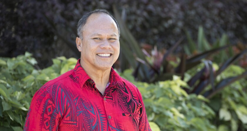 Eddie Maiava smiling wearing a red and black tribal-designed button-up shirt with greenery behind him.