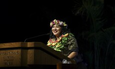 Melba Latu smiles at a wooden podium wearing a green Polynesian-designed dress with a flower crown and red, yellow and green-leafed lei around her neck with a black background.