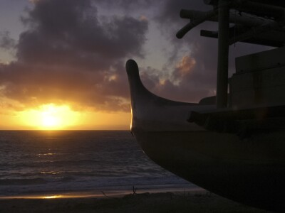 Silhouette of the Iosepa canoe hull against the sun rising above the ocean