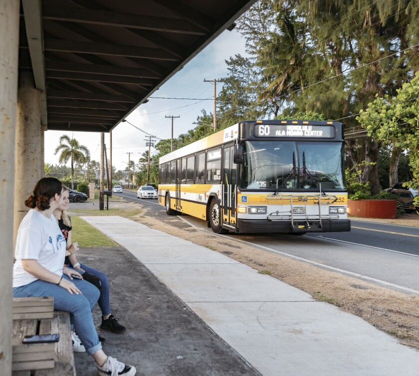 Two women sitting at a wooden bus stop with TheBus approaching on the road.