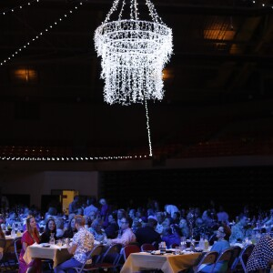 Employees sitting at dining tables below a white chandelier made of twinkle lights.