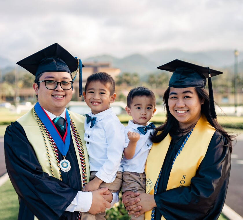 Dela Peña smiles with his wife both wearing black graduation caps and gowns with yellow sashes holding their sons wearing black shirts, and blue bowties with the BYUH campus in the background.