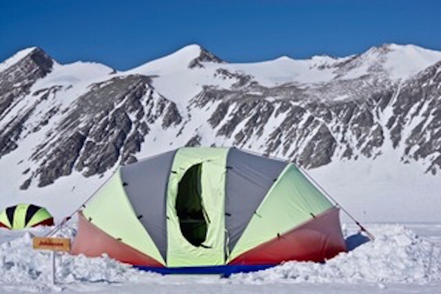 A tent at the base of a mountain range in Antarctica.