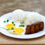 A photo of a seasider's breakfast. Two fried eggs, sausage links and two scoops of rice