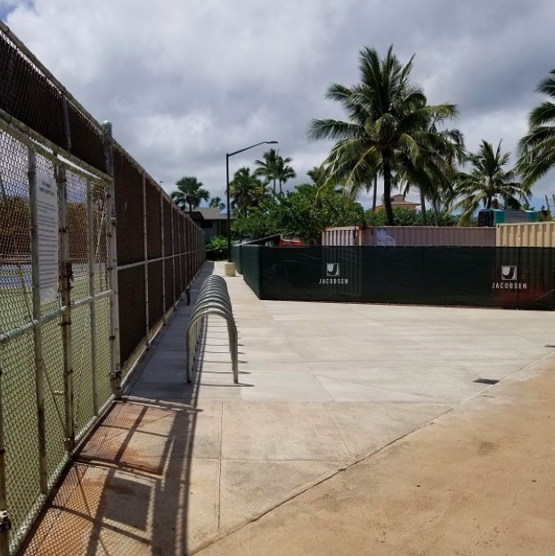 A narrow path between tennis court and construction black fences.
