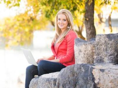 Whitney Tibbets sitting on rocks facing the camera with a laptop.