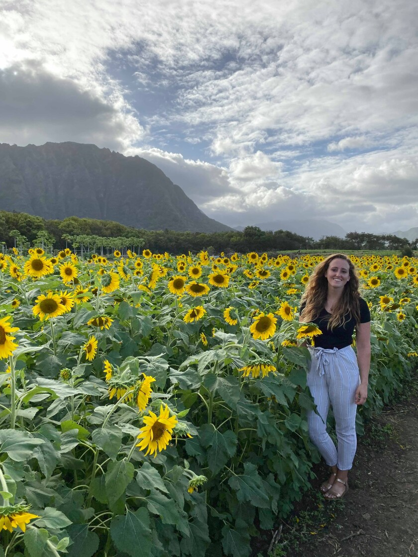 Hannah Howells stands in a sunflower field.