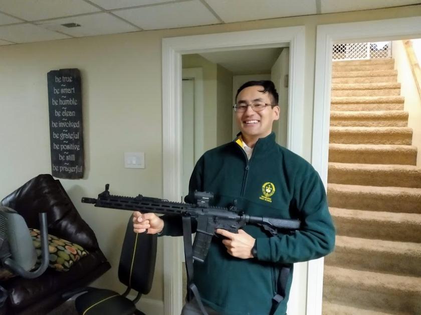 Ochirbat holding a gun wearing a green and yellow jacket in a house.