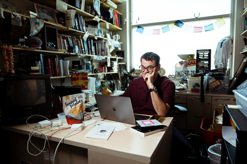 Portrait of English professor Eric Eliason in his office with snacks at his desk.