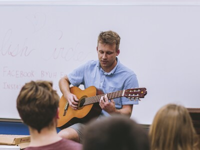An English Circle attendee plays the guitar in front of a gathering of students in a room.